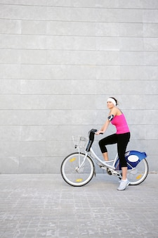 A young girl on a bike over grey urban background