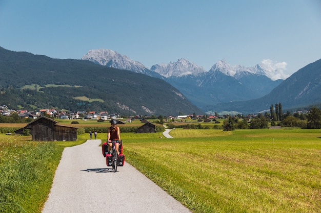 高山の谷の舗装道路で自転車に乗る少女。ヘルメット付きのサドルバッグを持ったサイクリスト。