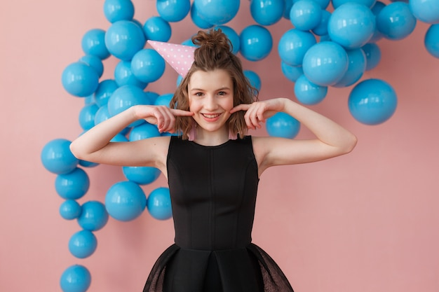 Young girl in a birthday hat posing holding fingers on cheeks at pink wall and blue balloons