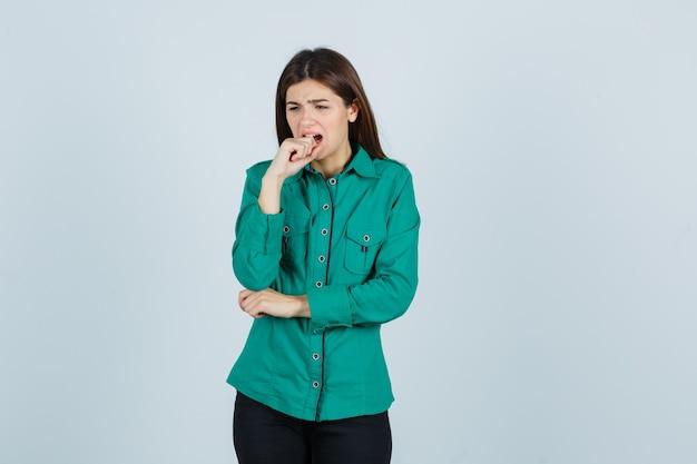 Ragazza che morde le dita emotivamente in camicetta verde, pantaloni neri e sembra preoccupata. vista frontale.