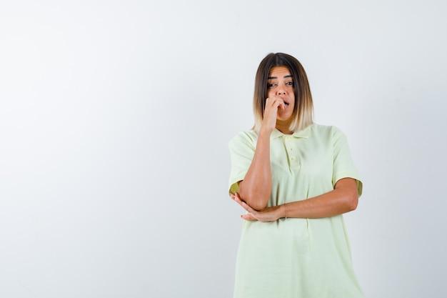 감정적으로 손가락을 물고, 티셔츠에 팔꿈치 아래 손을 잡고 무서워 보이는 어린 소녀. 전면보기.
