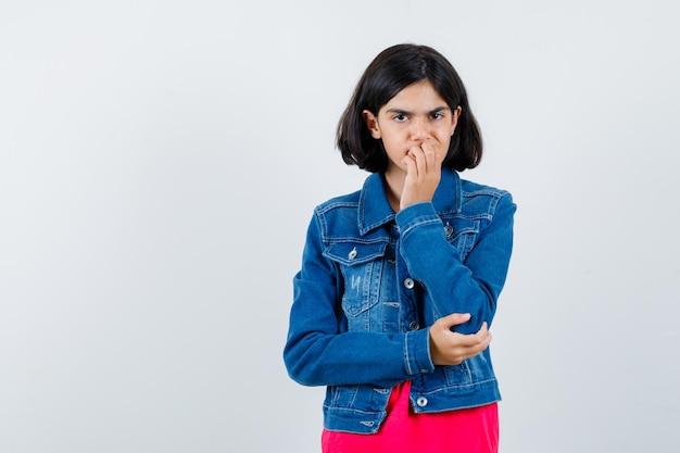 Giovane ragazza che morde il pugno mentre tiene una mano sul gomito in maglietta rossa e giacca di jeans e sembra eccitata, vista frontale.