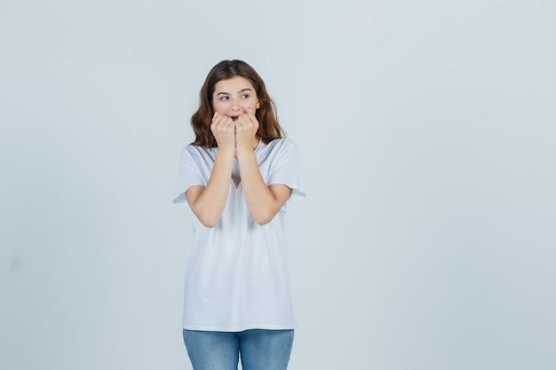 Молодая девушка эмоционально кусает кулаки в белой футболке и выглядит встревоженной. передний план.