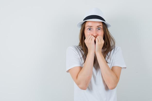 Ragazza che morde i pugni emotivamente in maglietta bianca, cappello e sguardo spaventato. vista frontale.