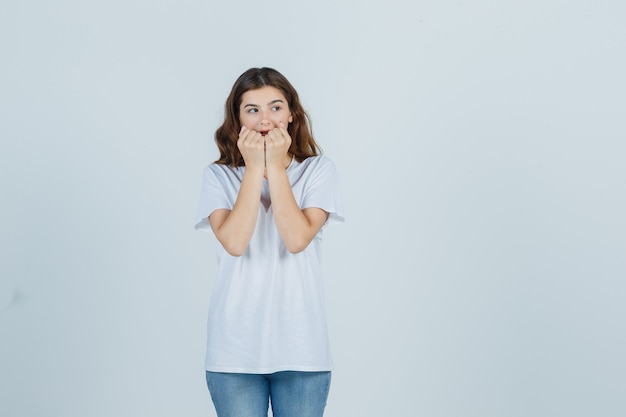 Young girl biting fists emotionally in white t-shirt and looking anxious. front view.