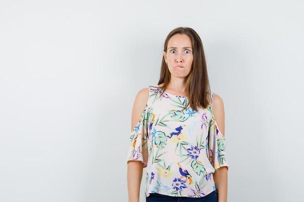 シャツ、ジーンズで唇を噛み、不安そうに見える少女、正面図。
