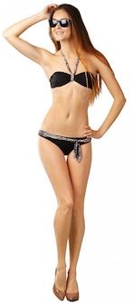 Young girl in black bikini posing on a white