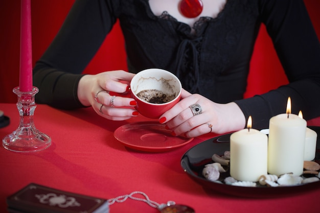 Young girl in a black dress is engaged in fortune telling on coffee grounds on red surface