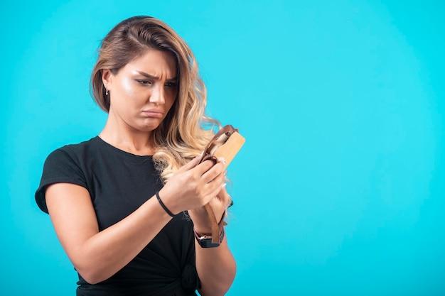 Una giovane ragazza in camicia nera si è appesa una macchina fotografica giocattolo al collo e l'ha controllata.