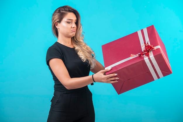 Giovane ragazza in camicia nera che tiene una grande confezione regalo. Foto Gratuite