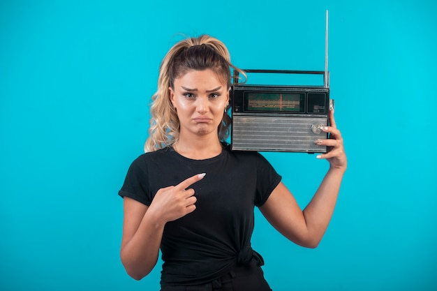 Young girl in black shirt holding a vintage radio on her shoulder and feels hesitating.