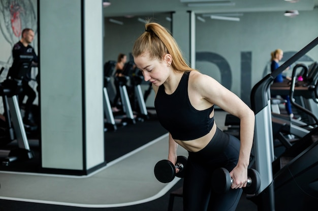 A young girl in black sportswear is engaged in the gym with dumbbells