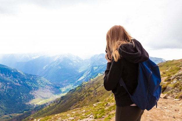 Young girl in a black sweater and leggings stands in the mountains and photographs the nature of beauty. travel and blogging concept.