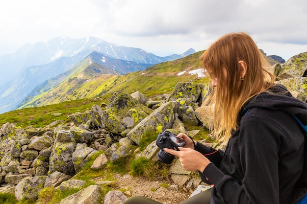 Young girl in a black sweater and leggings stands in the mountains and photographs the nature of beauty.