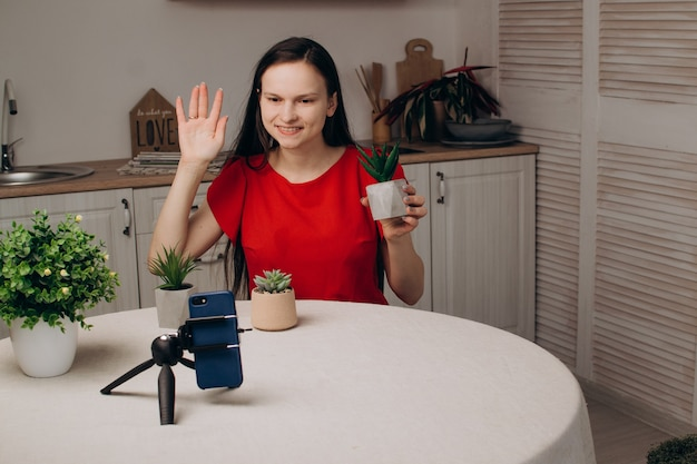 A young girl blogger is broadcasting live gardening in the kitchen