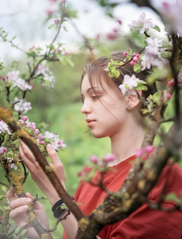 A young girl in a blooming garden looks at flowering trees
