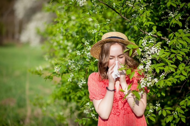 Young girl blowing nose and sneezing in tissue in front of blooming tree