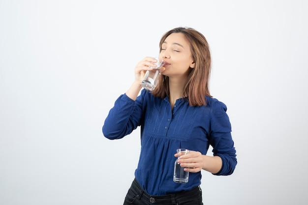 Young girl in blue blouse drinking glass of water on white wall.