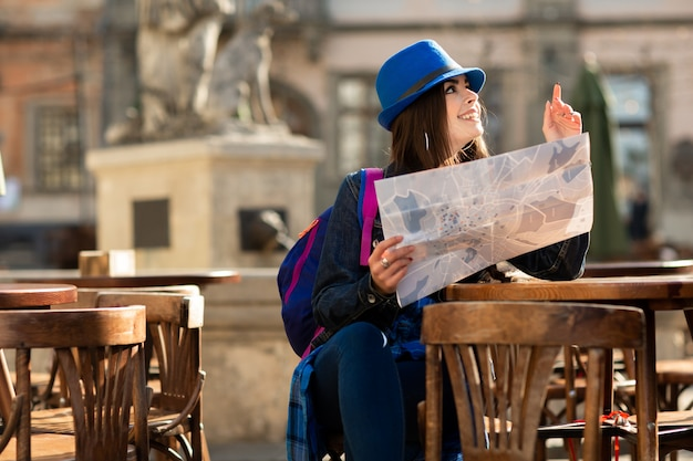 Young girl in a blue hat resting on the summer terrace in the old town, and looking at the map. lviv, ukraine