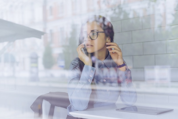 Young girl in blue shirt and glasses is talking on the phone, sitting in a cafe