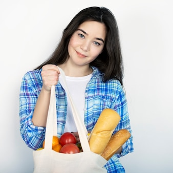 A young girl in a blue shirt holds a fabric bag with food