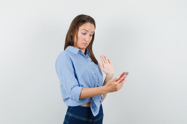 Giovane ragazza in camicia blu, pantaloni agitando la mano, tenendo lo smartphone e guardando confuso