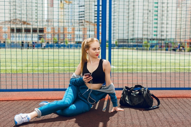 A young girl in a blue sport suit with a black top is sitting near fence on the stadium. she is listening to the music with headphones and looking far away.