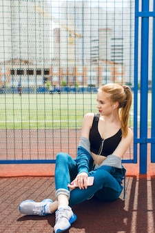 A young girl in a blue sport suit with a black top is sitting near fence on the stadium. she is listening to the music with headphones. she has an attractive figure.