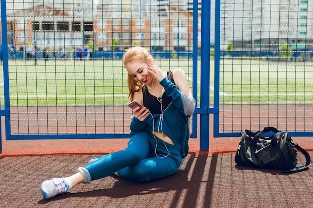 A young girl in a blue sport suit with a black top is sitting near fence on the stadium. she is listening to the music with headphones and smiling to the phone.