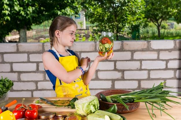 彼女がちょうど満たしたばかりのカラフルなガラスの瓶を賞賛して立っているさまざまな農場の新鮮な野菜を瓶詰めする少女