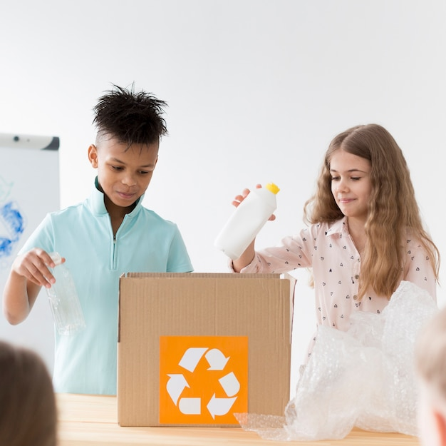 Young girl and boy learning how to recycle