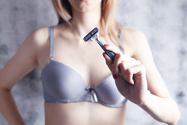 Young girl in bra holding a razor