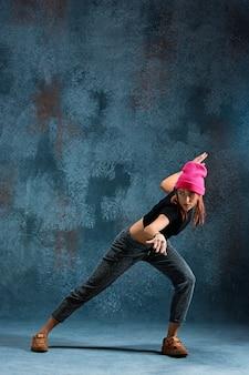 Young girl break dancing on blue.
