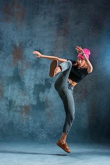 若い女の子の壁の背景にブレイクダンス。
