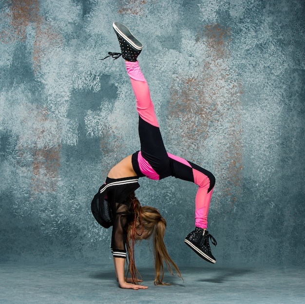 Young girl break dancing on wall