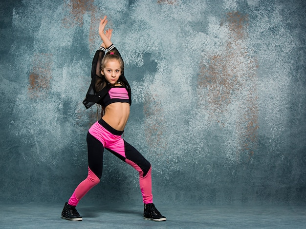 Young girl break dancing on wall.