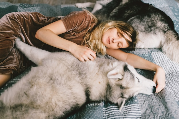 Young girl in brown dress lying on bed at home and sleeping with husky puppy. lifestyle indoor portrait of beautiful woman hugs husky dog on sofa. pet lover. cheerful female resting with adorable dogs.