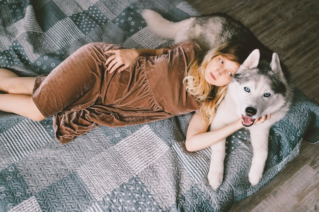 Young girl in brown dress lying on bed and hugs husky puppy. lifestyle indoor portrait of beautiful woman hugs husky dog on sofa. pet lover. cheerful female resting with adorable dog