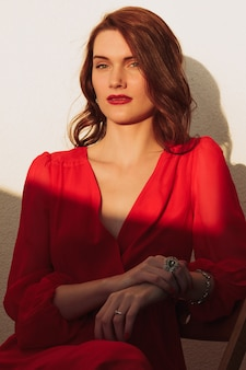 Young girl brunette standing on the balcony at sunset in a red dress and sunglasses