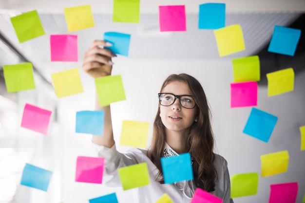 Giovane ragazza donna d'affari con gli occhiali guarda sulla parete trasparente con un sacco di adesivi di carta su di esso