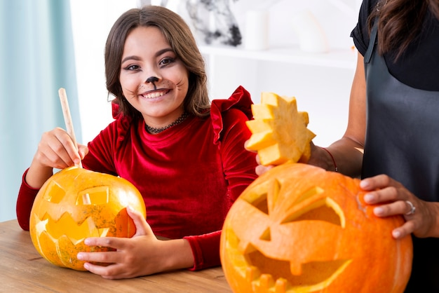 Young girl carving pumpkins for halloween