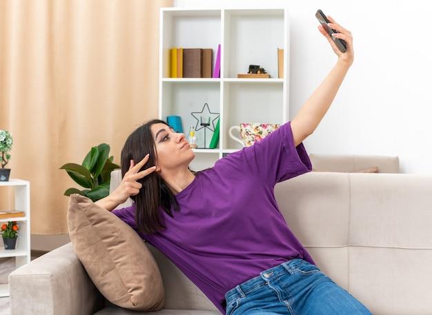 Giovane ragazza in abiti casual che fa selfie utilizzando lo smartphone che sembra sicura di mostrare il segno v seduta su un divano in un soggiorno luminoso