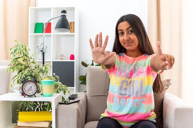 Giovane ragazza in abiti casual felice e fiduciosa che mostra il numero sei sorridente seduta sulla sedia in un soggiorno luminoso