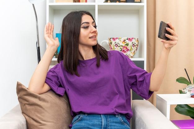 Giovane ragazza in abiti casual che tiene lo smartphone con una videochiamata felice e positiva che saluta con la mano che saluta seduta su un divano in un soggiorno luminoso