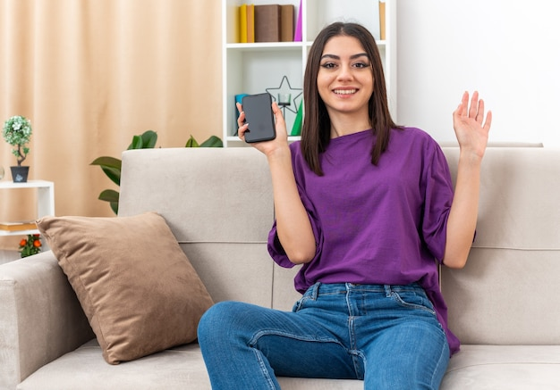 Giovane ragazza in abiti casual che tiene smartphone che guarda l'obbiettivo sorridente felice e positivo che fluttua con la mano seduto su un divano nel soggiorno luminoso