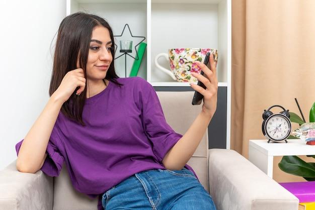 Giovane ragazza in abiti casual che tiene in mano uno smartphone che guarda con un sorriso sul viso seduto su una sedia in un soggiorno luminoso