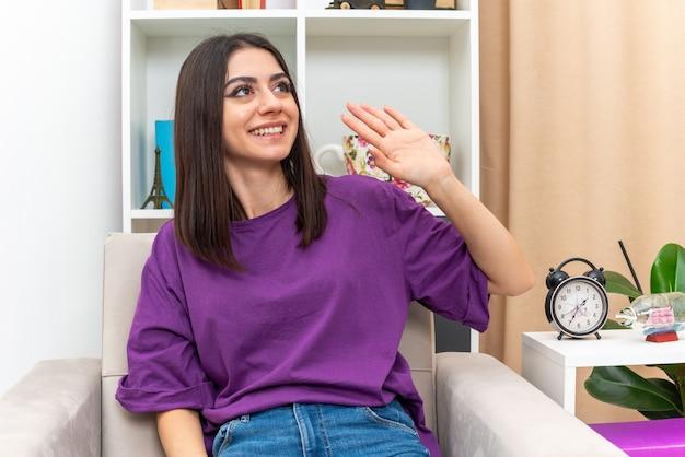 Giovane ragazza in abiti casual che guarda da parte sorridente amichevole che saluta con la mano seduta su una sedia in un soggiorno luminoso