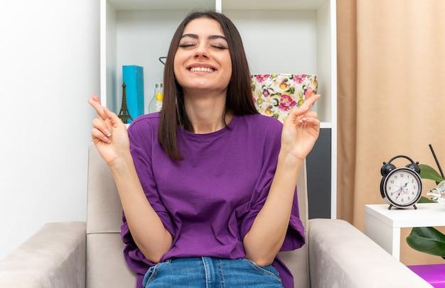 Giovane ragazza in abiti casual che esprime un desiderio desiderabile con gli occhi chiusi incrociando le dita seduta su una sedia in un soggiorno luminoso