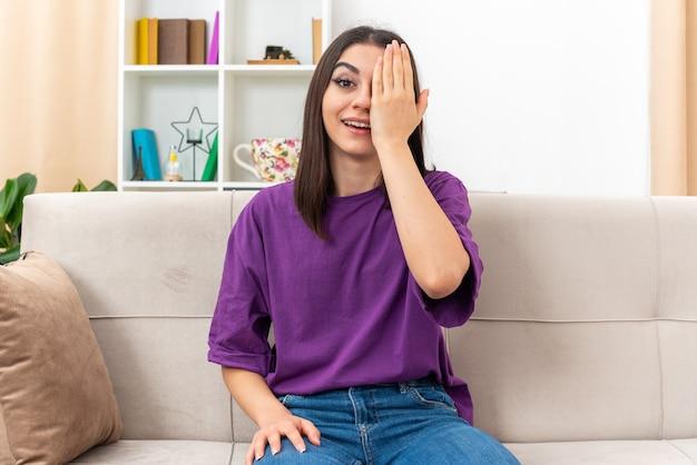 Giovane ragazza in abiti casual sorridendo allegramente coprendo un occhio con la mano seduto su un divano in soggiorno luminoso