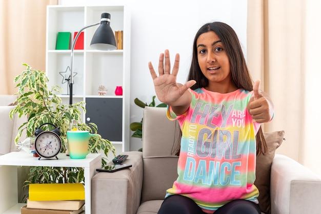 Giovane ragazza in abiti casual sorridente fiduciosa che mostra il numero cinque con il palmo che mostra i pollici in su seduto sulla sedia in un soggiorno luminoso